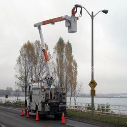 Maintenance vehicle repairing a street light